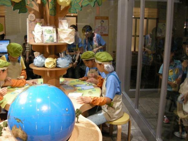 「キッザニア東京」内のエコショップを体験する子どもたち
