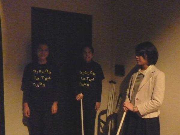 白杖を持ち、視覚障害を持つアテンドスタッフと共に暗闇へ