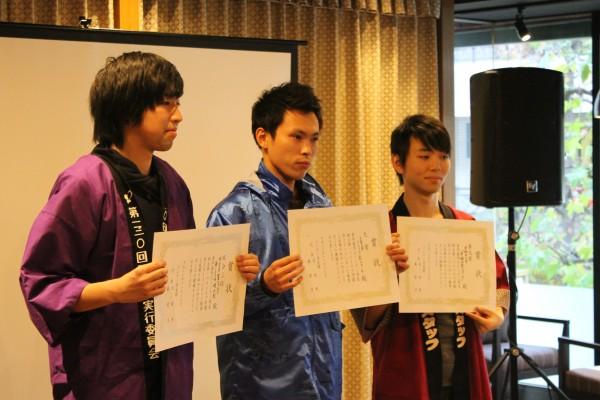 章を受賞した3校の委員長。左から、明治大学、上智大学、早稲田大学