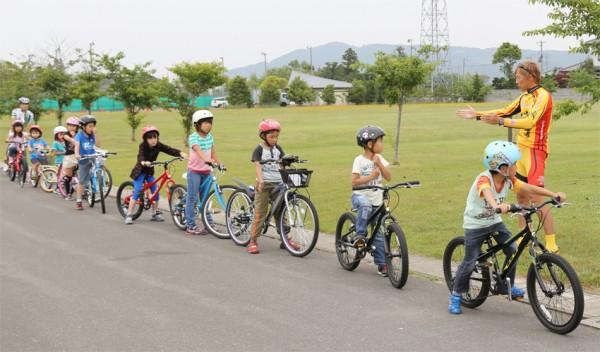 実際に自転車で走行練習。ブラッキー中島さんの説明を受ける子どもたち