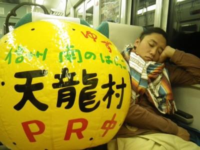 早朝の電車内で休んでいるときも天龍村をPRする雄大さん