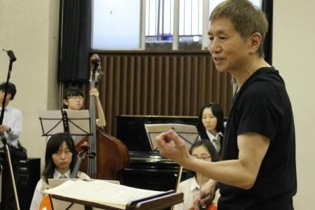 指揮台から部員に、各楽器の演奏の仕方を指示する高原氏=5月26日、都立三田高等学校で