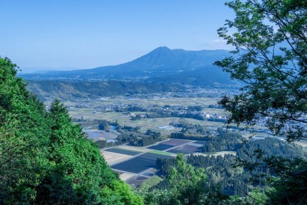 麓共有林の頂から見たえびの市の眺め。市内を流れる川内川を中心に、平野部分には田んぼや畑が広がる。奥に見えるは霧島連山の一角