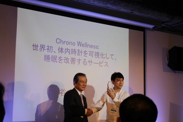 大賞に輝いた谷本さんには、副賞として100万円が贈られた。審査員長のMRIの小宮山理事長と=12月6日、グローバルビジネスデザインハブ東京で